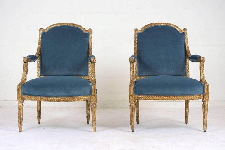 This pair of French Louis XVI style bergères dates to the 1860s. The carved frames are made of gilt wood with a beautiful distressed finish. The frames are adorned with decorative motifs, acanthus leaves, rosettes, and fluting. The seats have been
