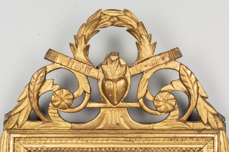 An early 19th century Louis XVI style French parcel giltwood bridal mirror from Provence. Nice hand carved crest with scrolling leaves and a flaming heart beneath a laurel wreath. All original with some restorations on the crest and some minor paint