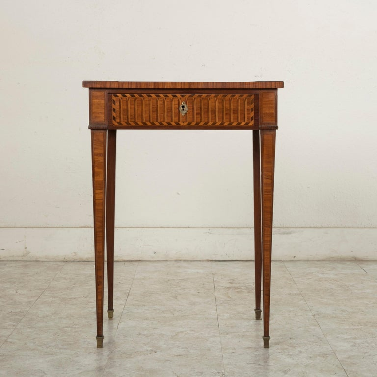 This late 19th century French Louis XVI style side table is constructed of mahogany with rosewood marquetry surrounded by fine lines of lemon wood inlay. Finished on all four sides, allowing it to be placed in the middle of a room, this piece