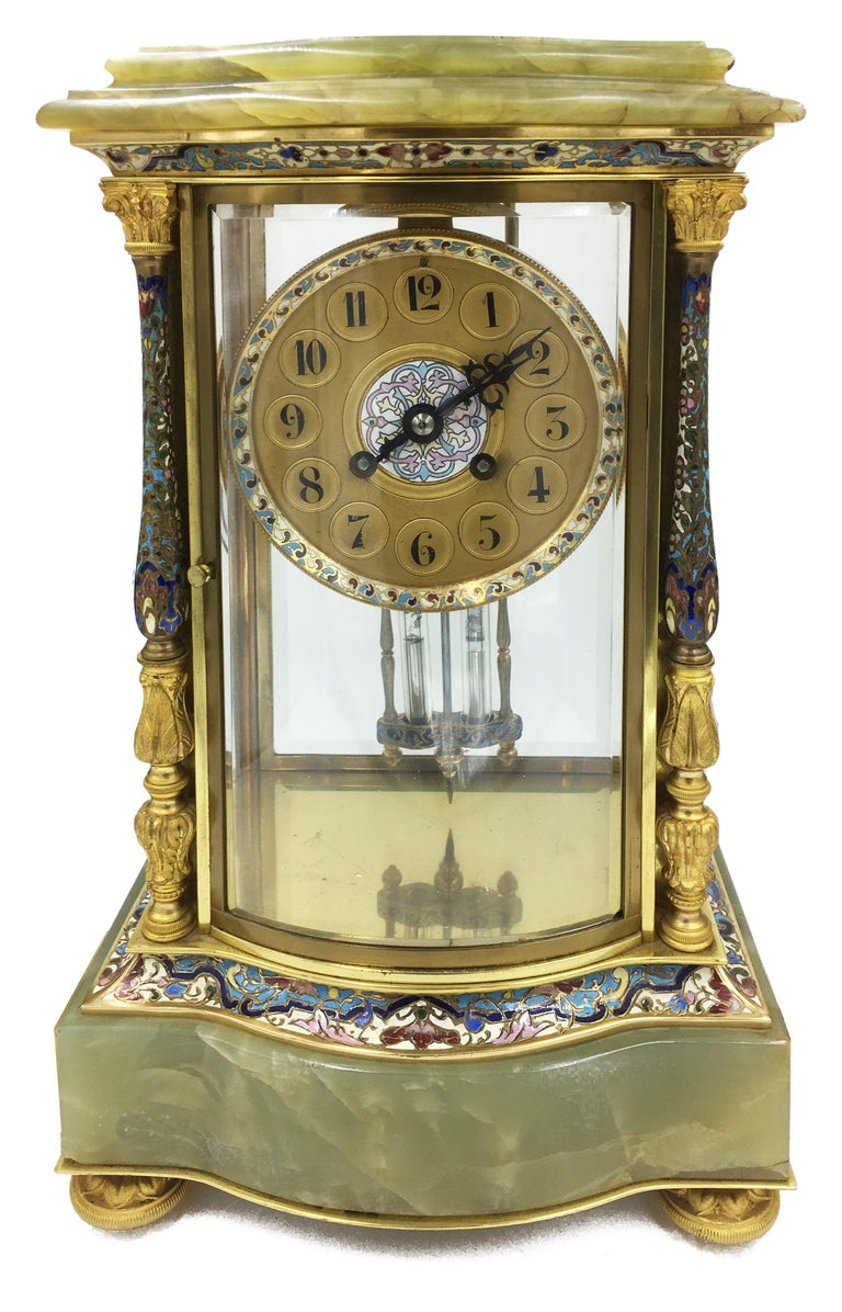 A very good quality French 19th century Louis XVI style onyx and champlevé enamel clock garniture, having a pair of Corinthian columns with enamel decoration either side of the gilded clock face, the movement being of eight day duration and chimes
