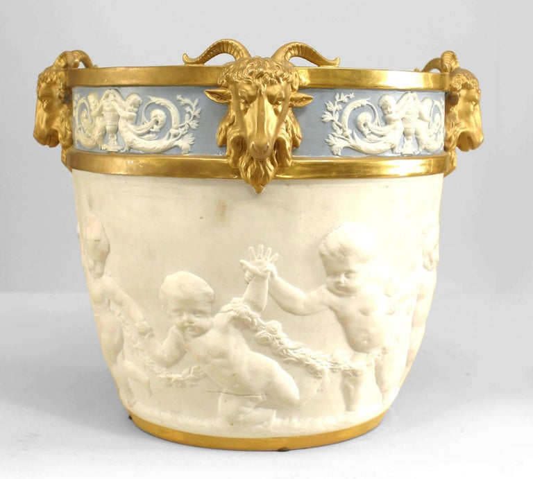 19th century French Louis XVI style blue and white Sèvres (Samson) porcelain jardiniere, decorated with neoclassical reliefs, such as putti, mermaids, and four gilt ram's heads.  Provenance: Estate of Evelyn Walsh McLean, Washington, D.C.