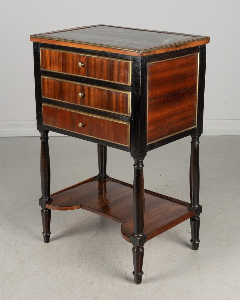 A 19th century French Louis XVI style side table or nightstand made of solid ebonized walnut and veneer of mahogany with brass trim. Three dovetailed drawers, lower shelf, turned legs and grey St. Anne marble top. All original. Marble has small