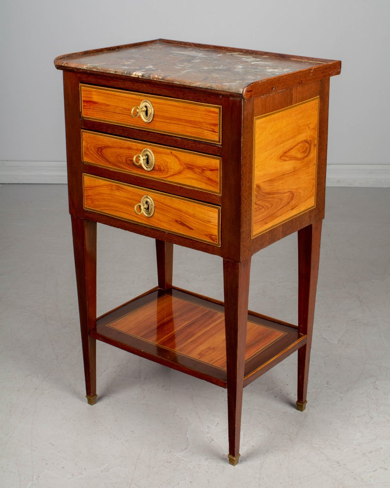 A fine 19th century Louis XVI style French side table or nightstand with marble top. Made of veneers of mahogany and tulipwood and finished an all four sides. French polish finish. Oak as a secondary wood. Three dovetailed drawers, with bronze
