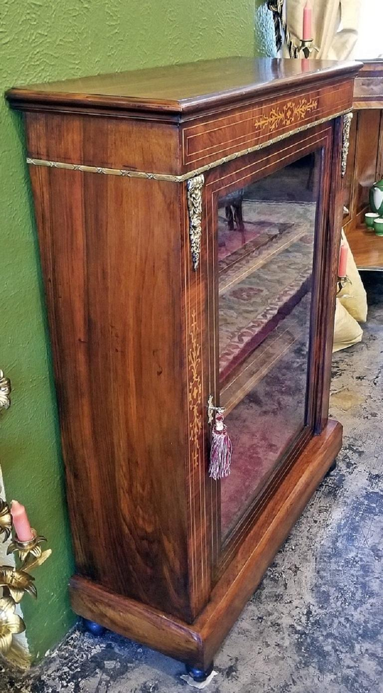 Lovely Louis XVI style glass and walnut vitrine or display case of neat proportions.  Beautiful ormolu mounts and trim. Burl and butterflied walnut.  Single door with satinwood stringing, three display shelves and re-finished with a luxurious