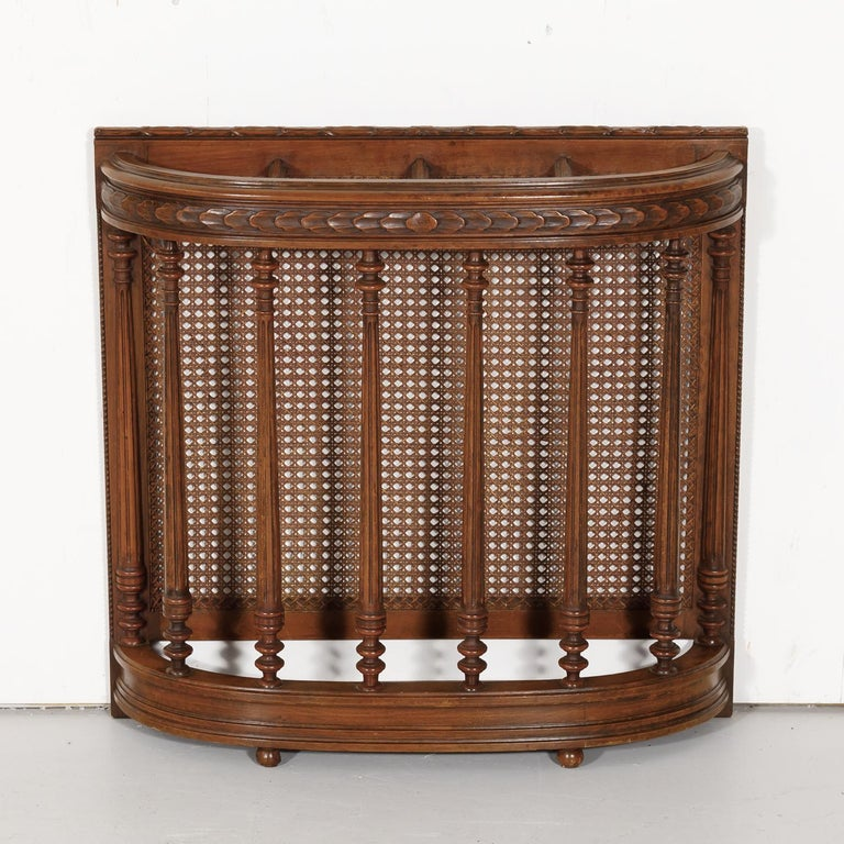 Handsome 19th century Porte-parapluie or umbrella stand handcrafted in Lyon of walnut with a cane back featuring typical neoclassical elements, circa 1890s. Made to stand against a wall, this umbrella stand is perfect for a small entry hall or mud