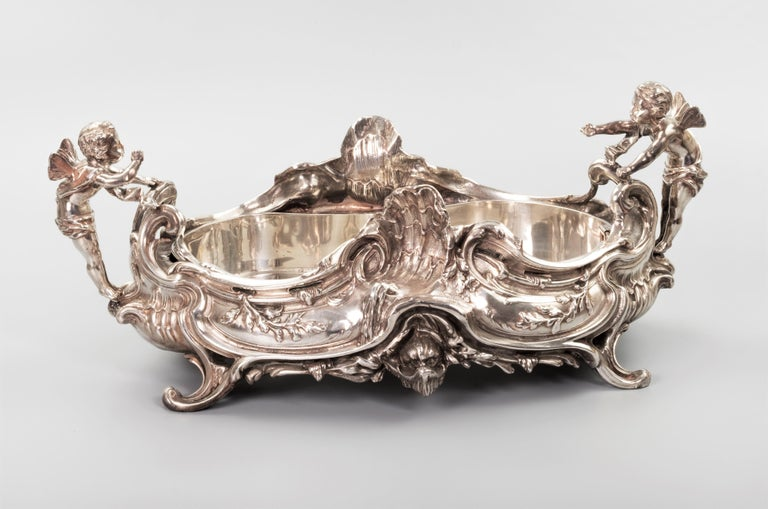 """This massive silver plated centrepiece is modeled in """"Rococo"""" style, with its famous """"C"""" and """"S"""" scrolls. Two putti on both side of the handle enlivens the whole piece as they were exchanging conversion over the dining table. The piece sits on a"""