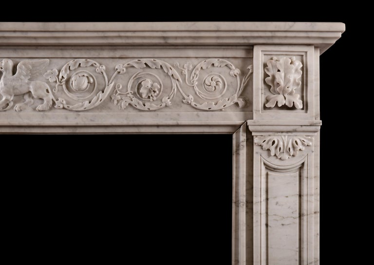 A French Louis XVI style Carrara marble fireplace. The frieze with carved foliage and swirling paterae throughout, with winged beasts and urn to centre. The jambs with shaped panel surmounted by end blocking with carved oak leaves. Plain moulded