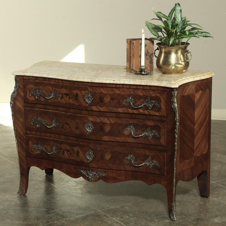 Exquisitely crafted during the latter years of the 19th century, this elegant French marble-top commode features subtle bowfront lines on the drawer facade and serpentine lines on each side. Lavished with mahogany veneer which has been oriented by