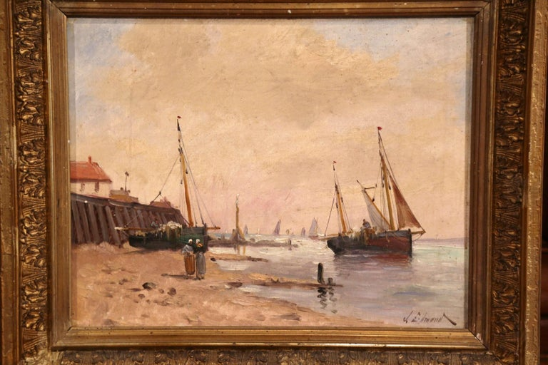 This colorful antique composition was painted in France, circa 1860. Set inside the original carved giltwood frame, the hand painted artwork depicts a beach scene off the Brittany coast. The composition shows fishing boat in the background and two