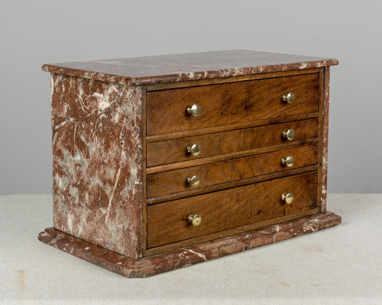 An unusual 19th century French miniature chest clad in Rouge Royal marble. Four dovetailed drawers are made of oakwood on the face and have polished brass knobs. Pine as a secondary wood. All original. Perfect for storing treasured objects or for