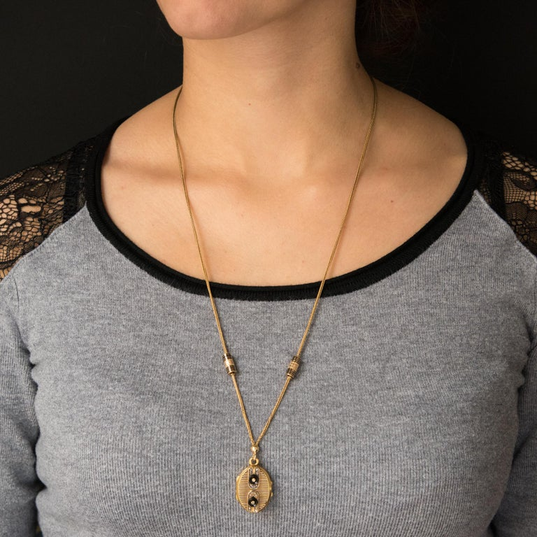 Pendant and its chain in 18 karats yellow gold, eagle's head hallmark. This splendid antique necklace is composed of a column mesh chain on which slide cylindrical enamelled runners of black and chiselled lines which abut on small rings. This
