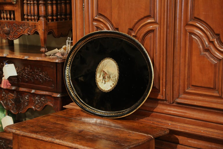 Elegant antique tray from France, circa 1870; oval in shape, the large black tole platter is embellished by hand painted gilt decor around the lip, and a colorful winter scenery in the center. The colorful scene features young children walking along