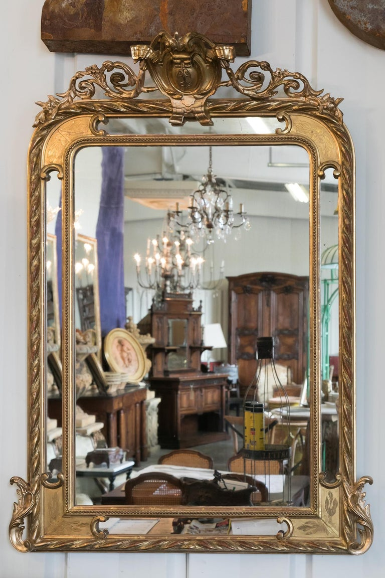 French Napoleon III period pareclose mirror with elaborately carved giltwood frame with red oxidation showing through. Decoration includes a central crest carved in high relief flanked by curving acanthus leaves and flowering branches with the inner