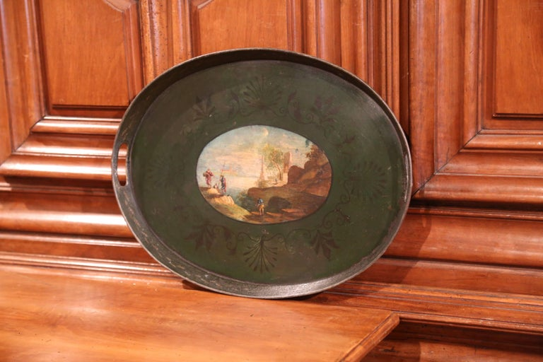 This elegant antique oval tole tray was crafted in France, circa 1870, the colorful platter with side handles, features an oval center medallion with coastline scene, cliffs, trees, fishermen and buildings in the background. The tray table is in