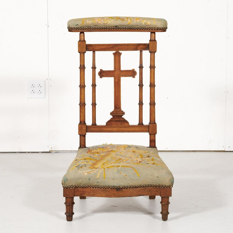 19th century French Napoleon III period prie dieu or prayer chair handcrafted and carved of solid walnut in Lyon, circa 1880s. This beautiful kneeling chair has its original covered, sloped top to rest one's arms or a prayer book with a hand carved