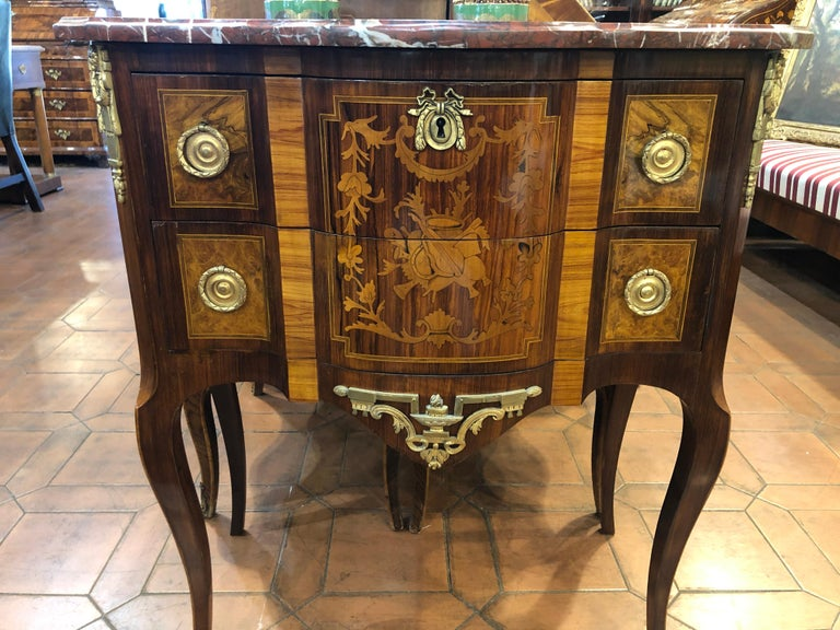 Small French chest of drawers in Louis XV style, Napoleon III era. Of excellent construction and inlaid in polychrome fruit woods, top in red marble. Restored and easy to position given its small dimensions. Two large drawers. Bronzes coeval to the