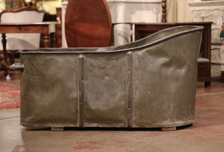 Use this decorative antique tub as a jardinière or a drink cooler! Crafted in France, circa 1880, and standing on a wood bottom, the oblong bathtub features a sturdy handle at one end and roll edges around the rim. The tub is in excellent condition