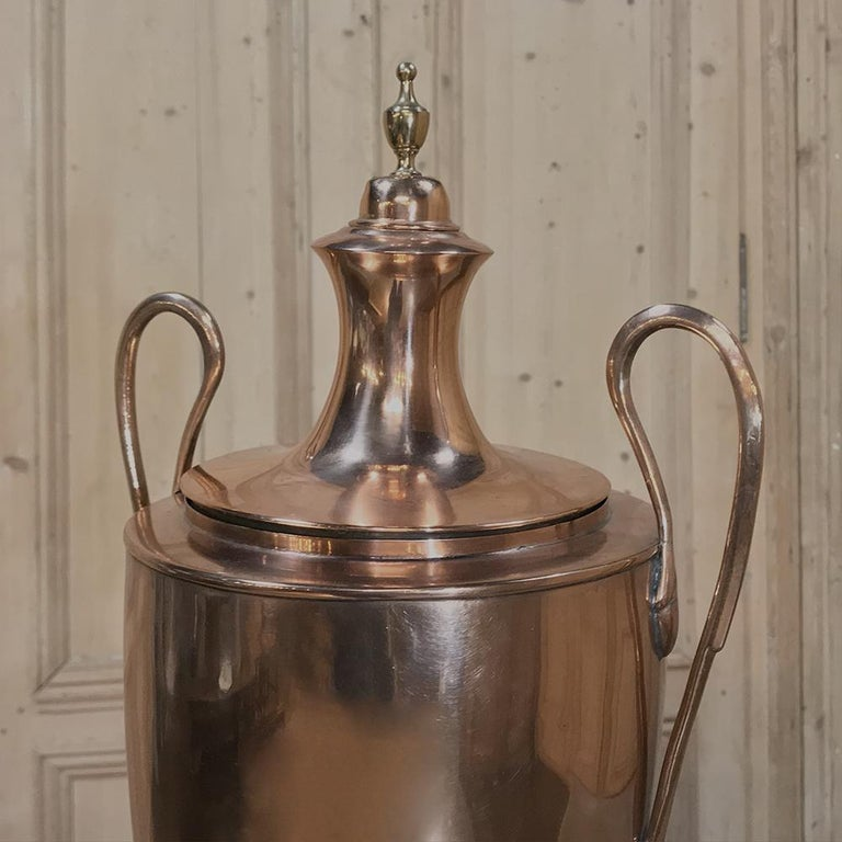 Elegant 19th century French neoclassical copper and brass tea server or coffee urn with a design inspired by ancient Greek Amphora. The urn featuring a lovely copper and brass body with two graceful swan-neck handles, and a brass finial on top of