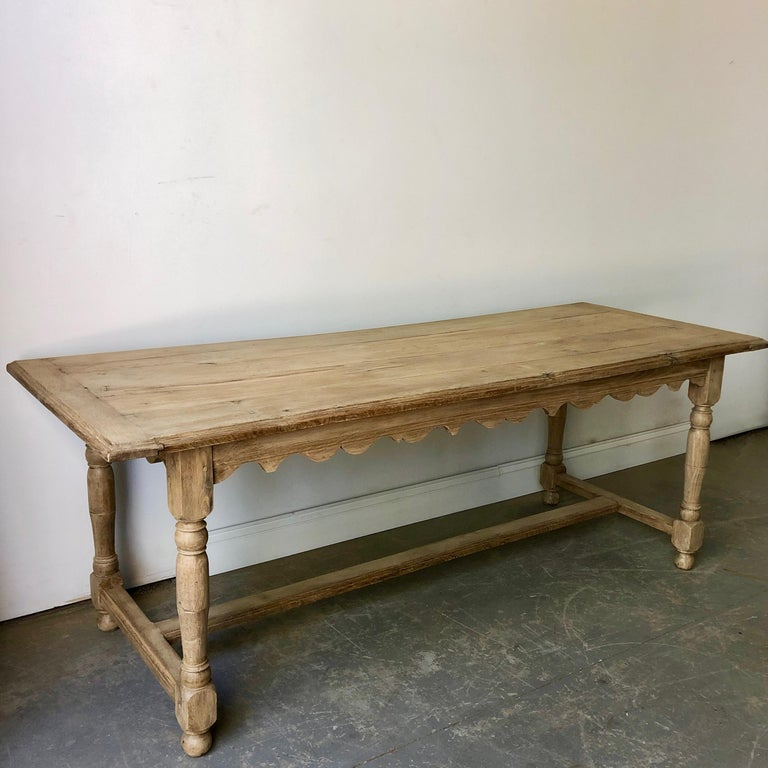 19th century French blond oak table with charming scallopped apron, baluster colums and strecher -- supporded on ball feet.