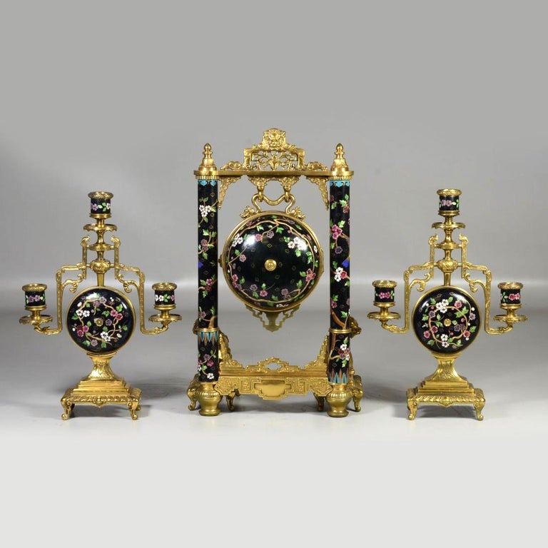 A fine chinoiserie gilt bronze and cloisonne three-piece clock set by Japy Freres. The ball encased movement hanging as a gong from a frame with bronze Chinese elements and cloisonne columns, with foodog supports with a pair of matching