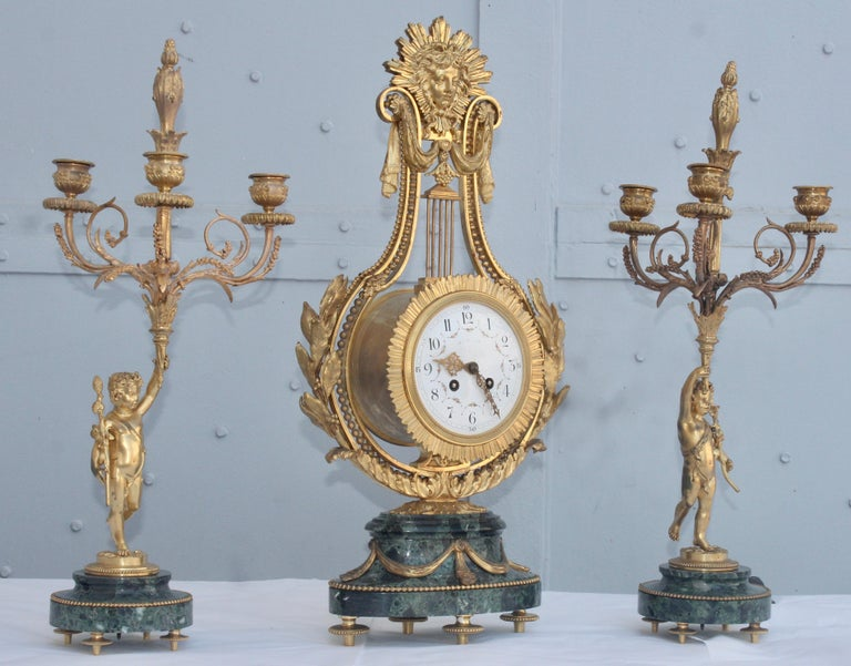 A 19th century French Ormolu and Vert de Mer marble three-piece lyre clock garniture The central clock is shaped as a lyre, and mounted all over with gilt bronze leaves and swags, surmounted by a sun mask on both sides, resting on green marble oval
