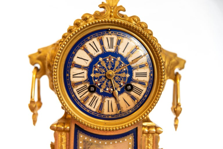 A late 19th century French Ormolu clock striking the hours and half hours on a single bell with gilding, dark blue and white porcelain dial. The case with urn shaped finial, lion mask ring drop handles, standing on scroll supports with guided