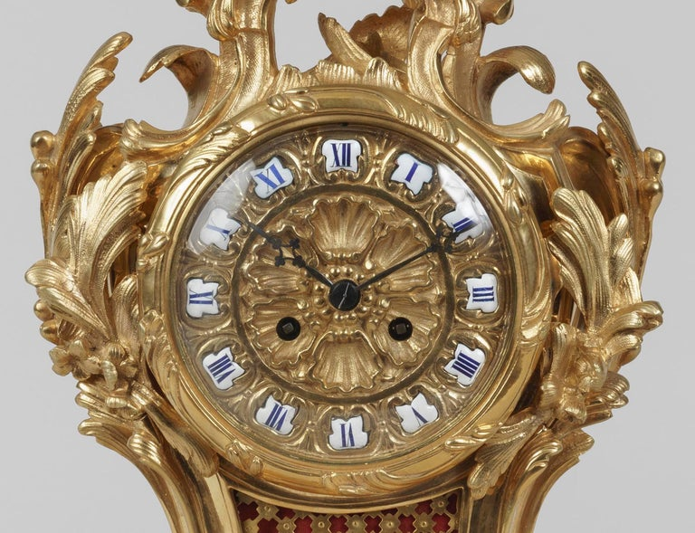 An Elegant Mantle Clock In the Louis XV Manner  The clock and its plinth executed in gilt bronze in a dynamic rococo style, rising from scrolling foliage, the dial in the shape of a flower and having the hours marked by hand-painted porcelain roman