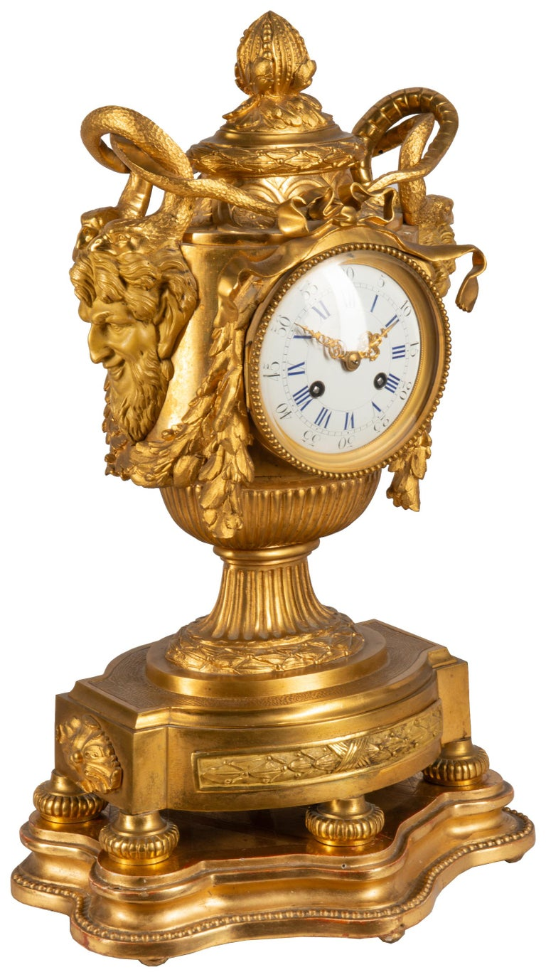 A very impressive 19th century French gilded ormolu Medusa influenced urn mantel clock. Having bearded masks to either side with serpents above foliate swags around the white enamel clock face, the movement being of eight day duration, chiming on