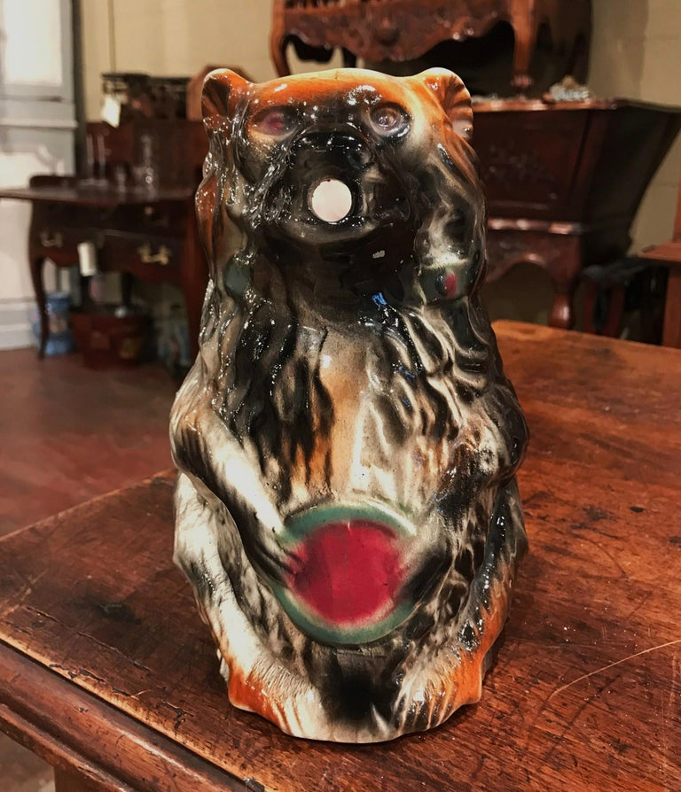 Add to a whimsical porcelain collection with this elegant antique Majolica pitcher. Crafted in southeast France circa 1890 in the faiencerie Coursange of Poet-Laval, the figural pitcher features a standing bear with his front arms resting on his