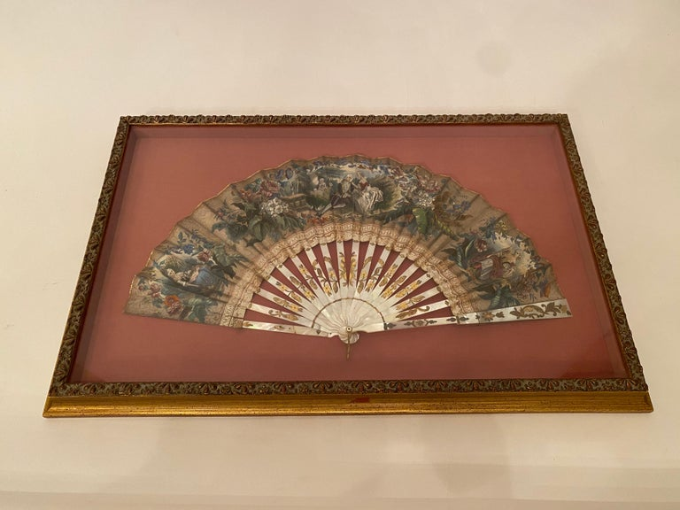 19th century French painted paper and mother of pearl fan, shadow-box framed antique ladies fan, made of mother of pearl with a hand embellished regency-style lithograph, with gold leaf on the outer edge. The mother of pearl sticks have etched brass