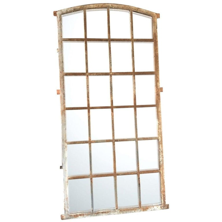 An antique pair of 24- field mirrored French Orangerie windows with a cast iron frame and a slightly arched top, in good condition. Metal aged frame and newly inserted mirror panels. The antique wall décor represents the Rococo time period. Wear