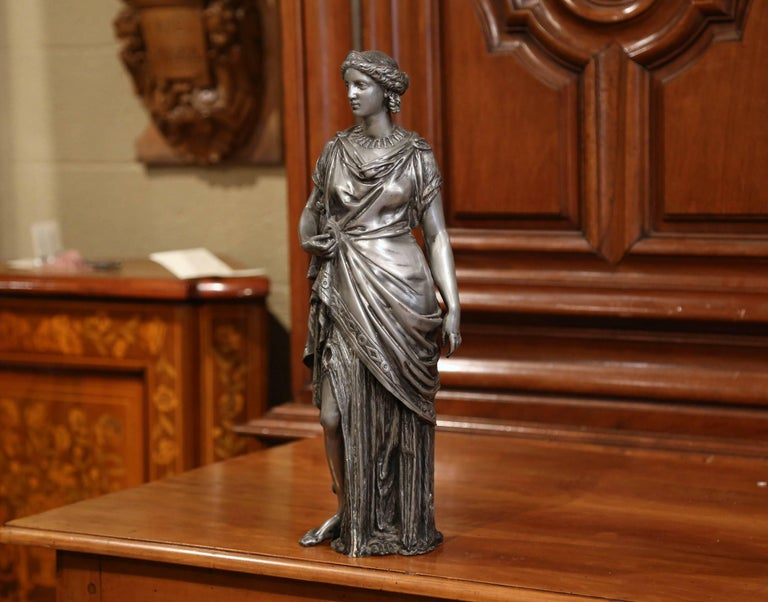 This elegant and detailed antique statue was sculpted in France, circa 1870. The beautiful, traditional sculpture made of pewter, features a Roman goddess figure dressed in elaborate clothing and jewelry. The figure sculpture is in excellent
