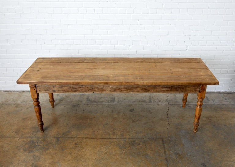 Rustic late 19th century French farmhouse harvest table or work table. Constructed from 1.5 inch thick planks of pine with breadboard ends on the top. Supported by large turned legs. The table is made with excellent joinery and craftsmanship being