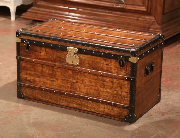 Rectangular in shape, this beautiful suitcase would make an elegant coffee table; crafted in Paris near the Champs Elysees, circa 1890 by Alexandre Velay, the fruitwood trunk with handles is finished on all four sides; it features decorative brass