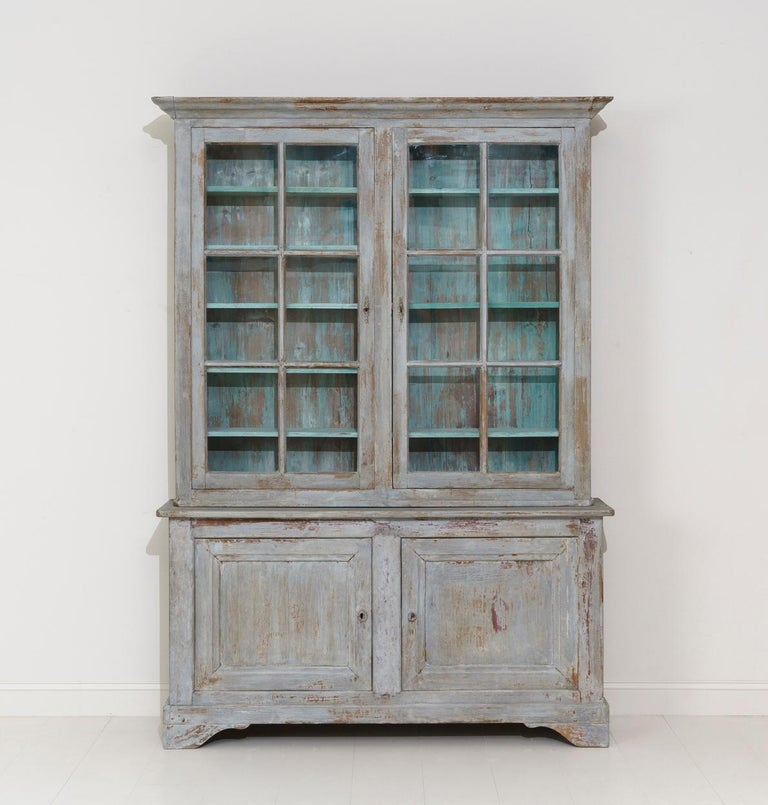 A beautiful French two-part painted library or bookcase in the Louis Philippe style with original glass from the Provence region of France. The exterior color of this buffet deux corps is blue - gray and the interior a French blue. The upper cabinet
