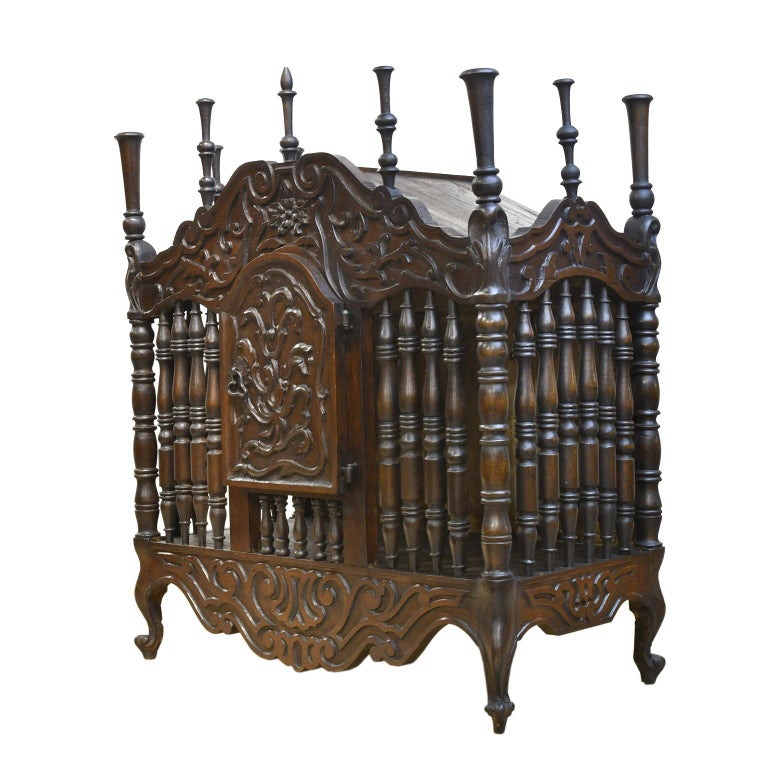 A very charming and rustic French Provincial bread cupboard or panetière in French chestnut. France, circa 1800s. This highly decorated box intended for storing bread has an arched bonnet, cabinet door and aprons embellished with floral, foliate and