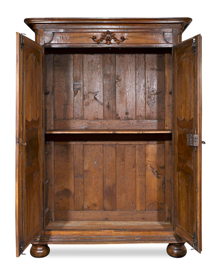 This fine French provincial double door armoire is beautifully crafted of fine walnut. Adorned with elegant, Rococo-inspired molding and featuring exceptional well-preserved, original hardware, this armoire provides ample storage space. The first