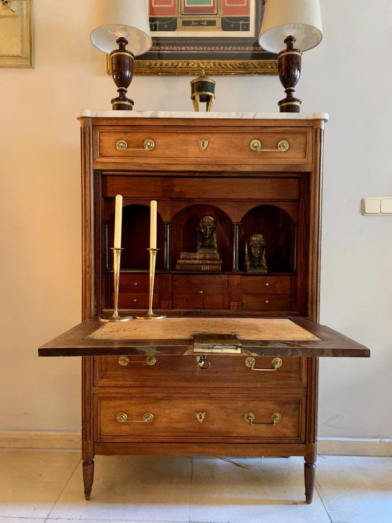 French Louis XVI secretaire desk in blond walnut with original white marble top, It has three drawers, one at the top and two at the bottom, on the front opens a table covered with original leather with five small drawers and small shelves with