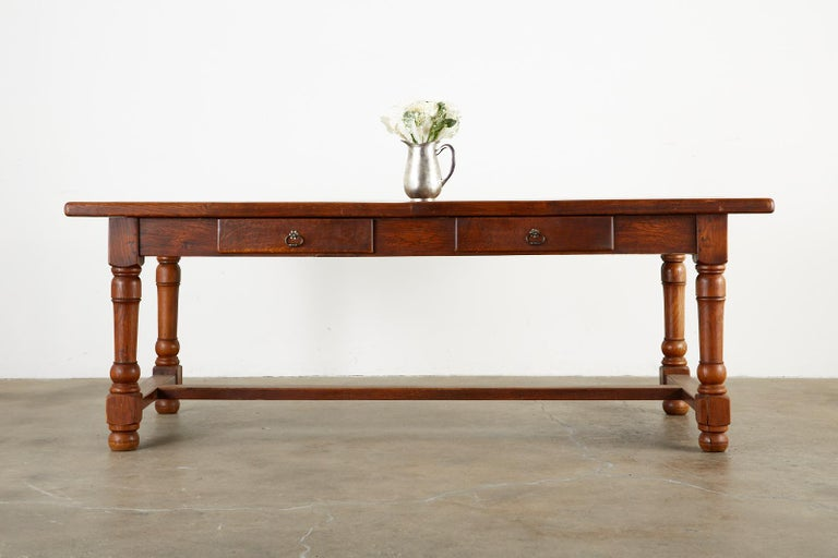 Quintessential 19th century country French Provincial farmhouse dining table. Constructed from rich oak with wood peg joinery. The top features 1.75 inch thick solid planks of oak with radiant grain patterns and knots. Supported by a substantial