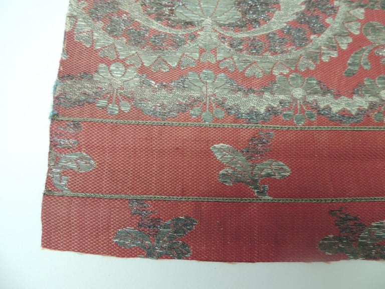 19th century French red and silver silk embroidered textile panel. Floral textile, silver metallic threads onto silk. Panel have a reinforce backing to make stronger if you decide to use it on a chair or to make pillows. Size: 17.5 x 17.5.