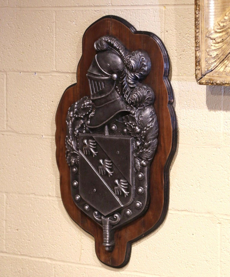 Decorate a study or a man's office with this elegant antique plaque. Crafted in France circa 1880, the wall decor features a coat of arms with a medieval royal knight armor with feather over a family crest with bird decor. The heavy shield is