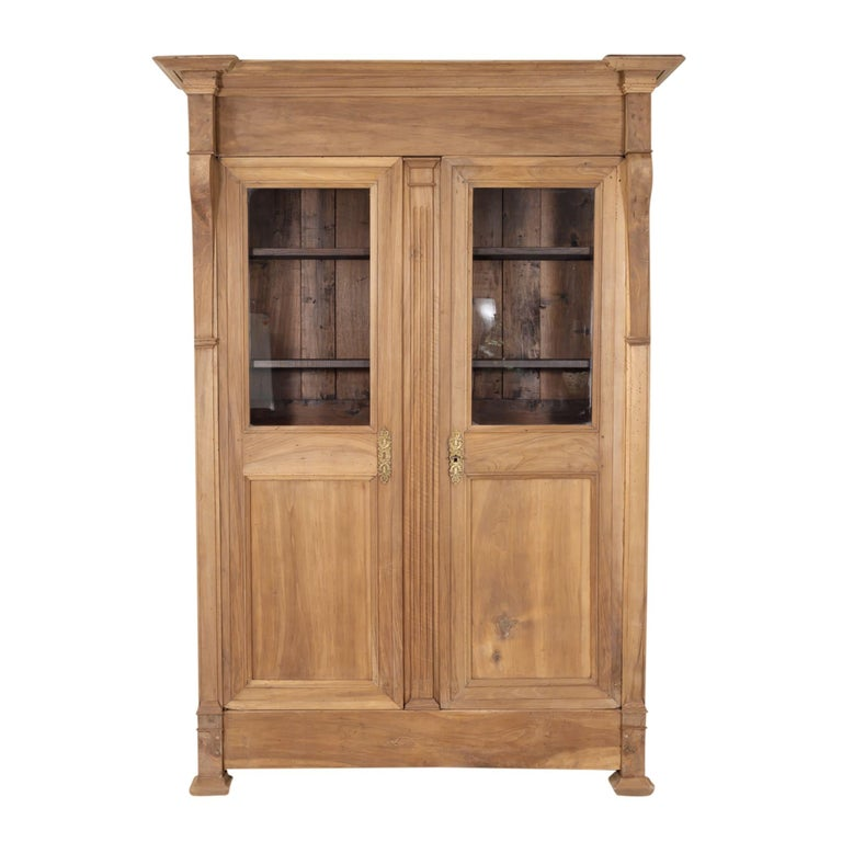 19th century French restauration period bibliotheque handcrafted of walnut in the South of France, circa 1820s. This handsome bookcase with its warm bleached patina features a stepped cornice over paneled doors with the original glass flanked by