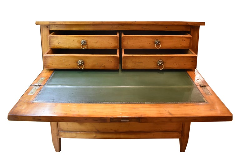 This 19th century narrow French Secretaire features a top drawer which opens to reveal a desk and four operable drawers. The Secretaire writing surface is green leather. The middle drawer is actually a cabinet and is hinged from the bottom. The only
