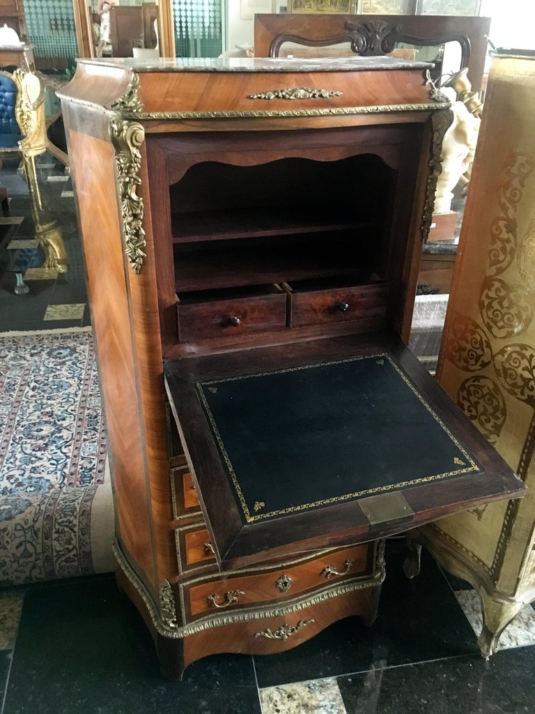 Small secretaire in doucine, curved on three sides, in veneer of precious wood inlaid in leaves in entourages of nets. It opens with four large drawers, a flap revealing two small drawers and shelves. Beautiful bronze trim and thin red marble