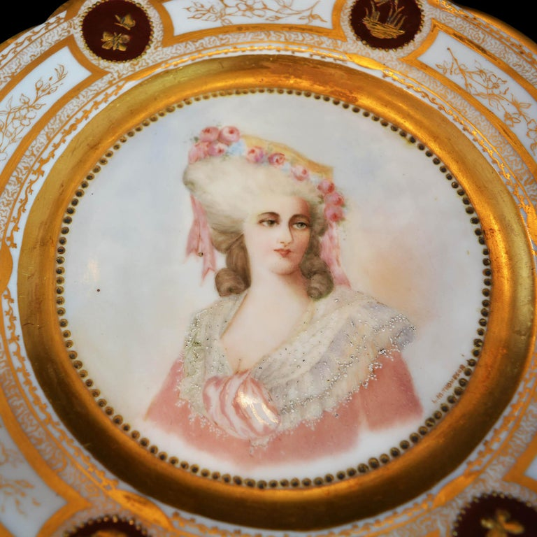Antique French portrait plate signed by the artist. It features beautifully painted woman with floral adorned hat, rim with gilt scalloped edges and decorated with gilt garden motif, en verso stamped
