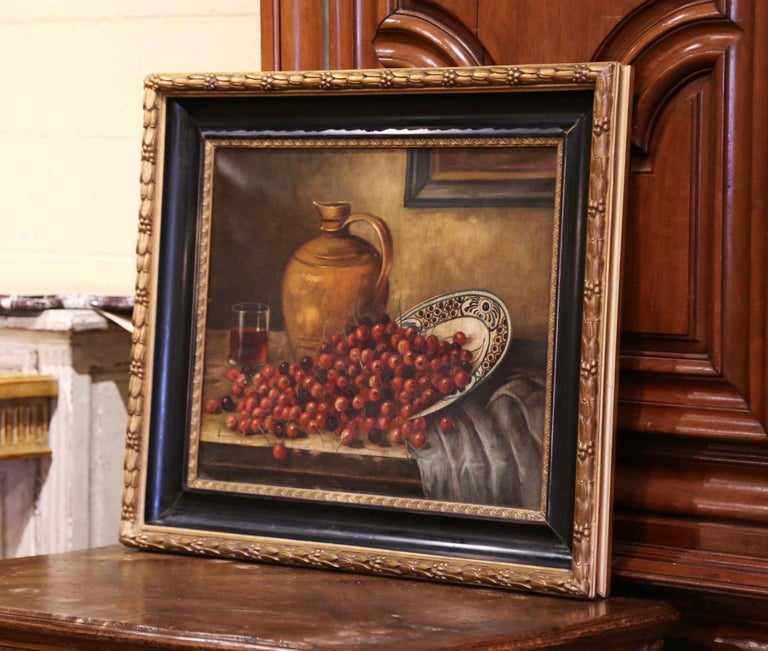 Hand painted in France circa 1880 and set in the original carved two-tone giltwood and blackened frame, the large art work depicts a table still life subject with grapes spilling out from a faience plate with a terracotta wine jug and a glass in the