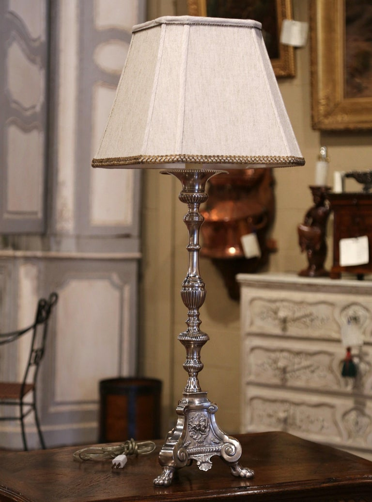 Created in France circa 1880, the elegant antique silver plated over brass candlestick stands on paw feet over a triangle base decorated with angel face medallions and shell decor, it has been fitted into a table lamp with new wiring embellished