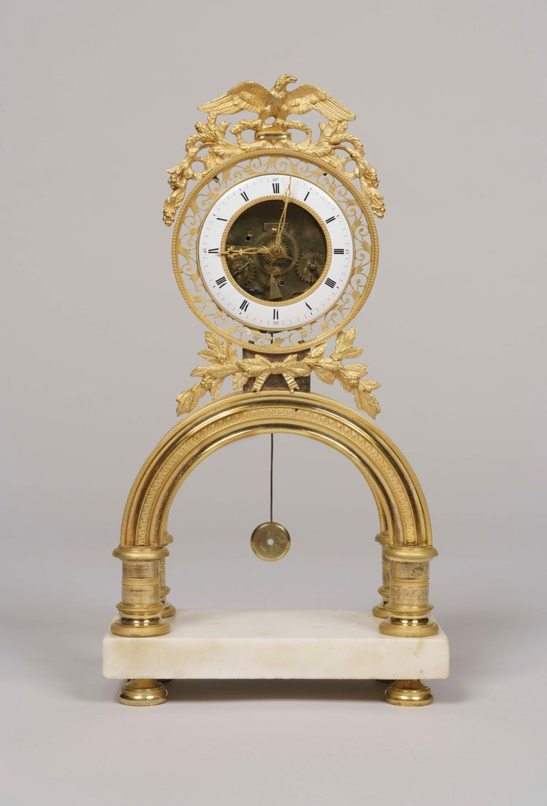 A symbolic skeleton clock from the French Directoire period.  A rectangular Carrara marble plinth with bronze toupie feet with knurled decoration supports an ormolu 'arc-de-ciel', with the circular clock over, dressed with garlands; the white enamel
