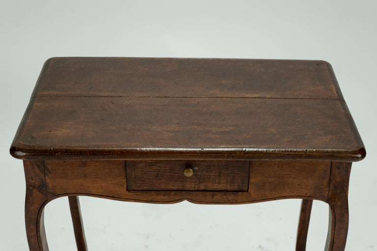Louis XV walnut table with cabriole legs and a small drawer.
