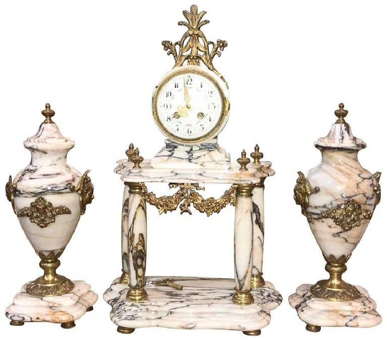 Exquisite 19th century French three-piece clock set. The veined marble clock with four columns, flame finials and mounted with finely detailed bronze appliques of festoon swags and caryatid masques. The clock is flanked by similarly decorated ovoid
